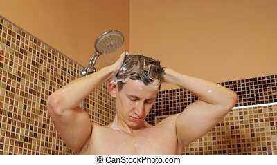 Handsome man washes his head in the shower.