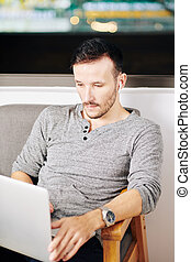 Handsome man watching movie on laptop
