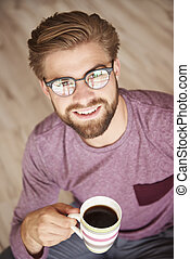 Handsome man wearing glasses drinking coffee