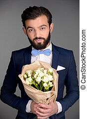 Handsome man with beard holding bouquet of flowers