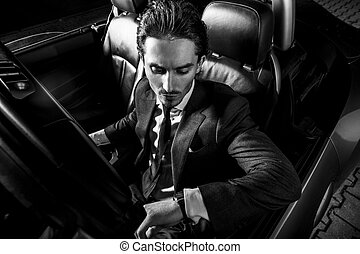 Handsome man with beard in suit driving car - Man with beard...