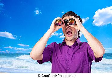 Handsome man with binocular near sea.