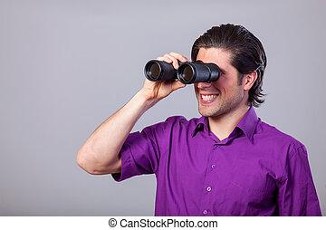 Handsome man with binocular on gray background.