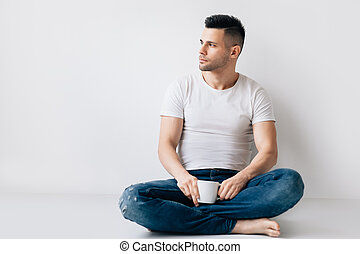 Handsome man with cup of coffee relax sitting on floor