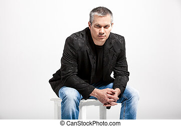 Handsome man with gray hair sitting on chair - Portrait of...