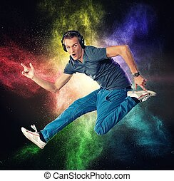 Handsome man with headphones jumping against colourful powder explosion