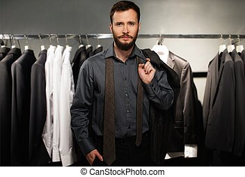 Handsome man with jacket over his shoulder in a clothing store