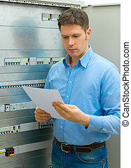 Handsome man with manual near electrical industrial panel.