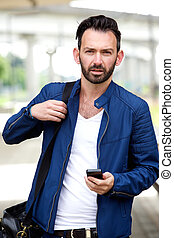 Handsome man with mobile phone outdoors