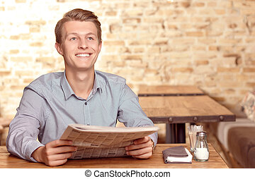 Handsome man with newspaper in cafe