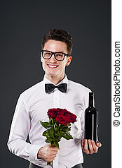 Handsome man with red wine and bouquet of roses