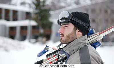 Handsome man with ski walking in snow