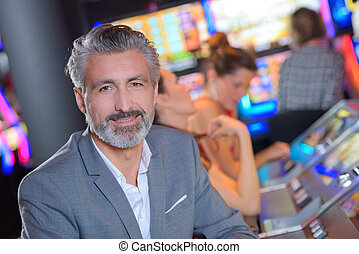 handsome man with slot machine in the casino