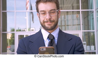 Handsome man with smart phone technology app looks at camera...