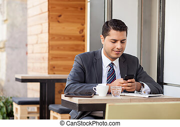 Handsome man with suit is using telephone in cafe