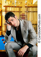 handsome man with suit sitting in billiard pool