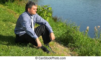 handsome man without coat sitting on bank