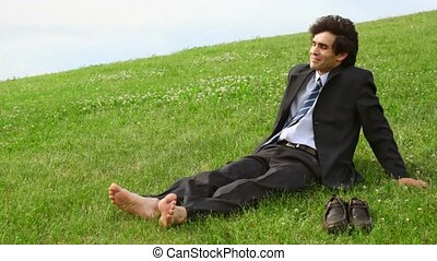 handsome man without shoes sitting on green grass
