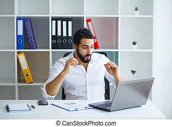 Handsome man working on project at modern office desk