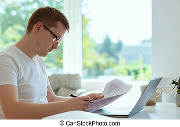 Handsome man works at home with his laptop