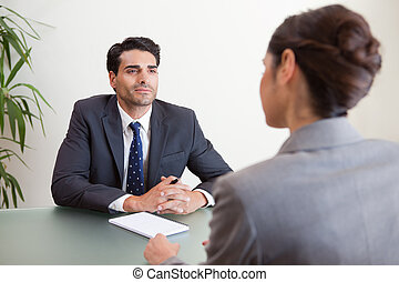Handsome manager interviewing a female applicant in his...