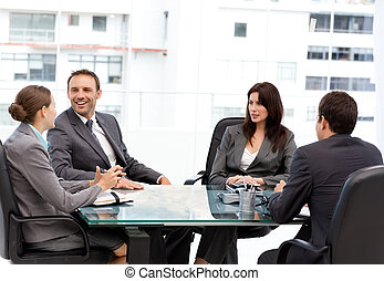 Handsome manager laughing during a meeting with his team