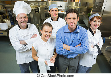 Handsome manager posing with some chefs and waitress in a...