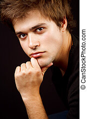 Handsome masculine man with hand at chin