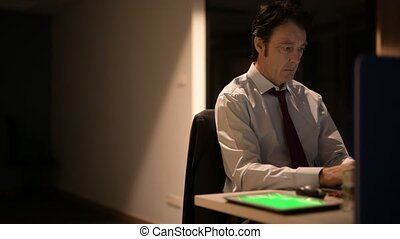Mature Businessman Sitting And Working In Office At Night