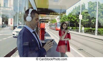 Handsome mature businessman waiting for tram, listening...