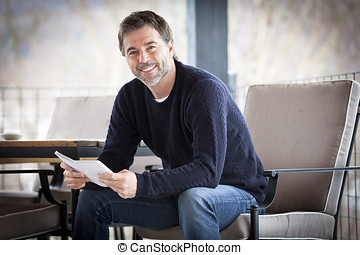 Handsome Mature Happy Man Smiling At The Camera.Outside. Reading a book