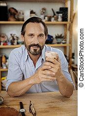 Handsome mature man drinking tasty coffee at work