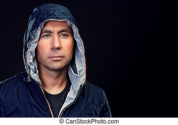 Handsome mature man in hooded jacket looking at camera.