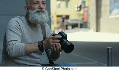 Handsome mature man smiling while photographing outdoors -...