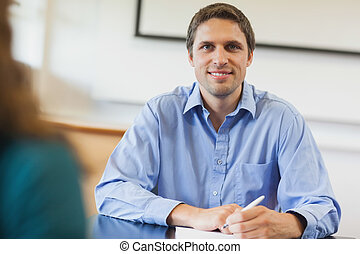 Handsome mature student sitting in classroom smiling at ...