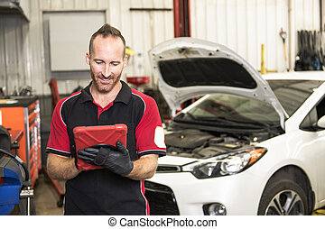 handsome mechanic based on car in auto repair shop with tablet on hand