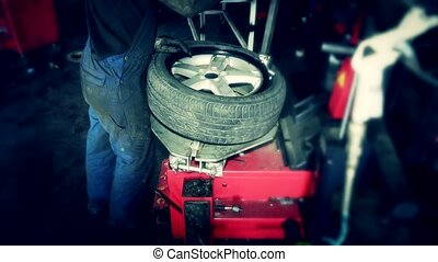 handsome mechanic fixing tire in car service garage.