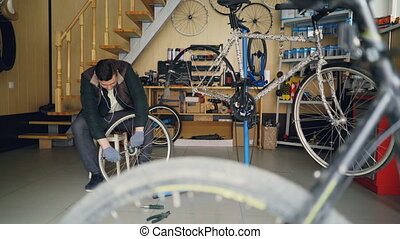 Handsome mechanic is fixing back wheel with wrench while...