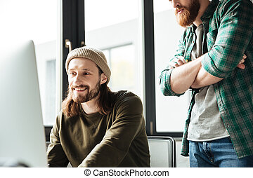 Handsome men colleagues in office using computer - Image of...