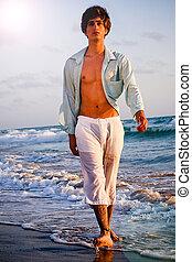 men walk on the beach