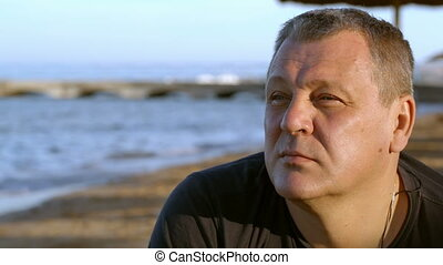 Handsome middle-aged man thinking at the beach