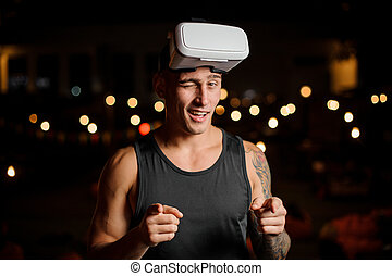 Handsome muscular and tattooed man in night vision glasses winks