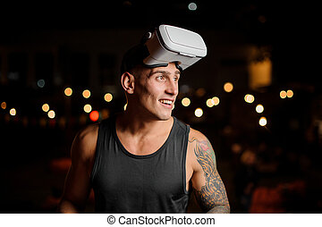 Handsome muscular and tattooed smiling man in night vision glasses looks away