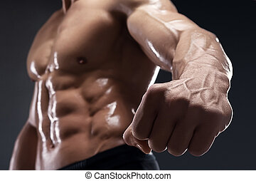 Handsome muscular bodybuilder shows his fist and vein. -...