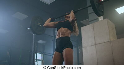 Handsome Muscular female Does Deadlift and Curls with a Heavy Barbell. Athletic Shirtless Woman Training, Doing Power, Strength and Endurance Exercises with Barbell. Workout in the Hardcore Gym. High quality 4k footage