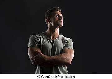 Handsome muscular fit young man on dark background looking up