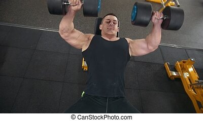 Handsome muscular man does dumbbells exercises in a gym