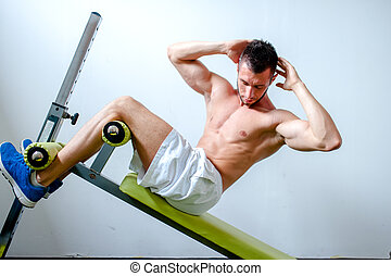 Handsome muscular man doing sit-ups on a incline bench