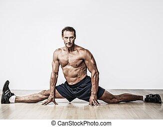 Handsome muscular man doing splits