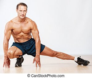 Handsome muscular man doing stretching exercise.